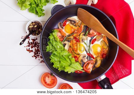 Fried eggs in pan with salad tomato pepper and spice on wthe table