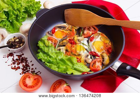 Fried eggs in pan with ingredients on wooden background