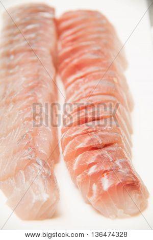 Fresh fish sashimi on a white dish textured desk.