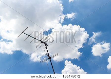 old TV antenna on roof photoblue sky background