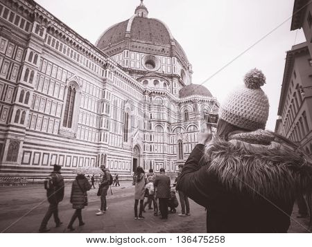 monochrome woman with hat taking pictures in Florence Italy