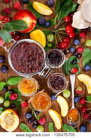 Jam And Berries On Rustic Wooden Background.