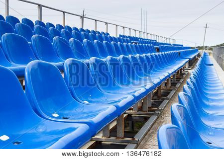 Empty plastic blue chairs at stadium in a row