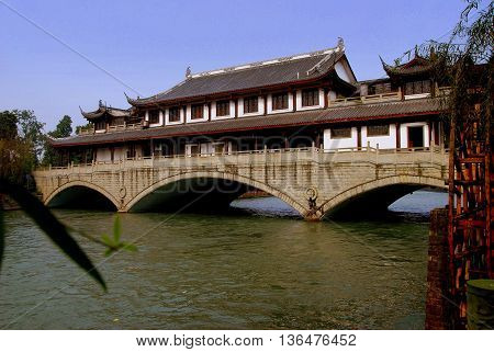 Sandaoyan China - November 10 2007: A vast hall with flying eave roofs built over the stone three span Yanqiao Bridge on the Baitiao River