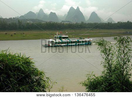 Guang Xi Province China - April 29 2006: Sightseeing boat sailing between Guilin and Yangshou passes dramatic karst rock formations lining the Lijiang River