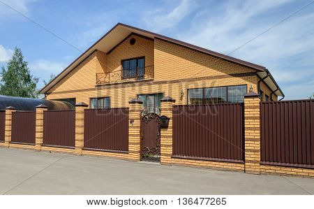 Big yellow brick cottage with balcony and brown metal fence sunny day