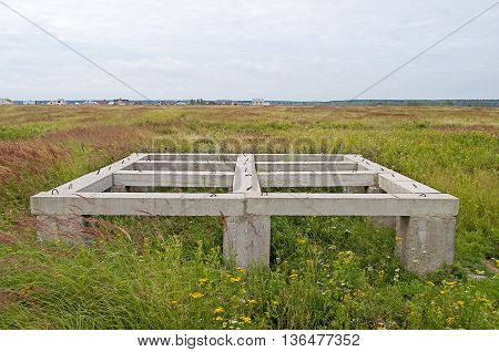 Concrete pier foundation of small country house in the meadow on summer