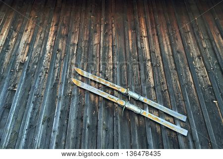 A pair of old style vintage wooden skis with strap binding hanging on rustic wooden barn wall
