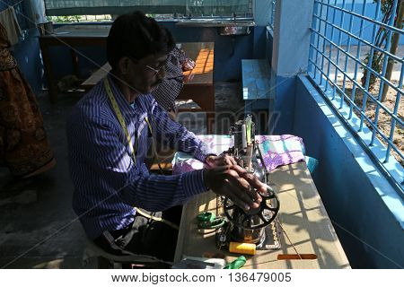 KUMROKHALI, INDIA - FEBRUARY 13: Man is working with sewing machine in Kumrokhali, West Bengal, India on February 13, 2014