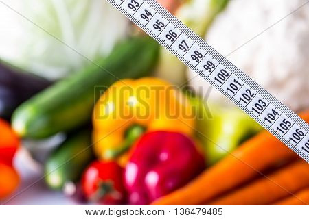 Measuring tape and Fresh vegetable and fruits in the background. Healthy diet concept.