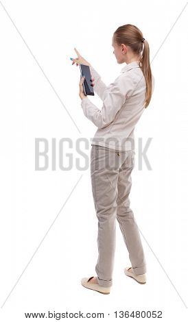 back view of standing young beautiful  girl with tablet computer in the hands of. girl  watching. A girl in a white jacket vertically holding a tablet PC, and shows his left hand into the distance.