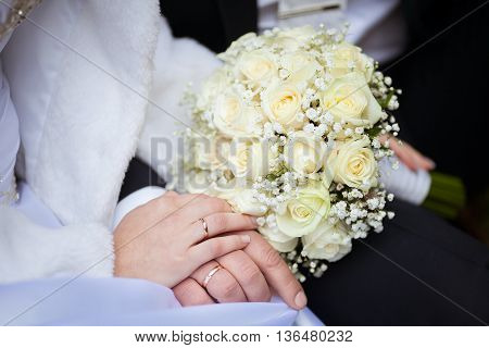 Picture a pair of newlyweds holding a wedding bouquet