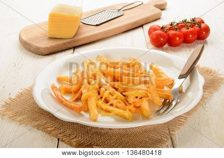 golden brown french fries with melted cheese and fork on a white plate