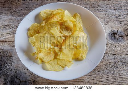 Chips in a white plate on a wooden background.