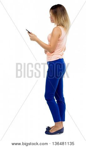 back view of standing young beautiful  girl with tablet computer in the hands of. girl  watching.  Blonde girl in blue pants is standing sideways and looking at tablet computer.