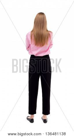 back view of standing young beautiful  woman.  girl  watching. Rear view people collection.  backside view of person.  The girl office worker in black pants standing with her hands folded on his chest