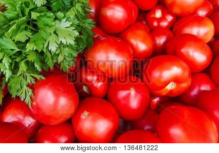 Horizontal top view close up of many cherry tomatoes at the market near a bunch of green parsley