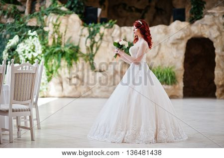 Charming Red-haired Bride With Wedding Bouquet At Hand Posed At Great Wedding Hall With Caves And Ve