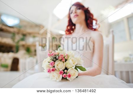 Wedding Bouquet At Hands Of Charming Red-haired Bride Model Sitting On Chair At The Table On Great W