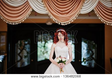 Charming Red-haired Bride With Wedding Bouquet At Hand Posed Against The Background Of Coffee Curtai