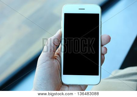 Hand holding white smartphone in coffee cafe
