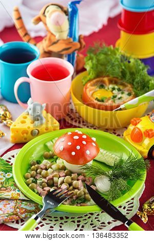 Fun food for kids with salad baked tomatoes stuffed with egg and berry drink on a laid table decorated with toys and candies