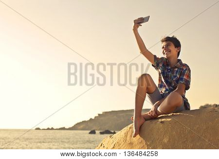 Young boy doing a selfie at the beach