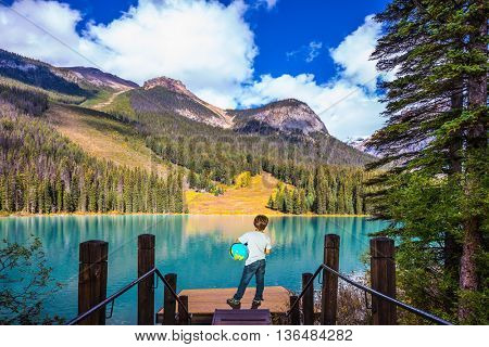 Emerald Lake in Yoho National Park in the Canadian Rockies. The seven-year slender boy with the globe in hands admire nature.