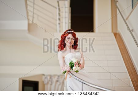 Charming Red-haired Bride With Wedding Bouquet At Hand Posed On The Stairs With Metal Railing At Gre