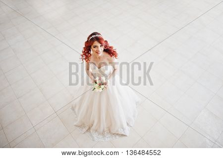 Top View Of Charming Red-haired Bride With Wedding Bouquet At Hand Posed Against Wgite Tile On The G