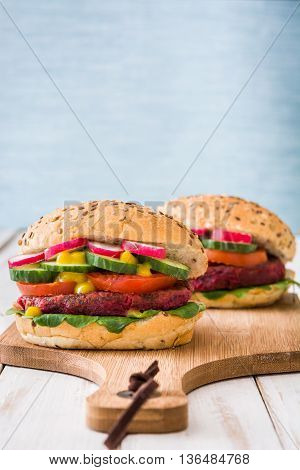 Veggie beet burger on white wooden and blue background