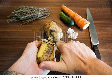 Male hands peeling yellow potatoes peeler on the kitchen.
