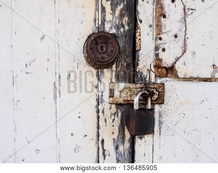 Rusty knob and master key lock the wood door