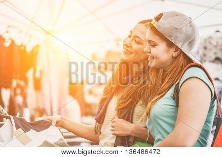 Young women doing shopping at the weekly cloth market at sunset - Cheerful girls enjoying sale time in summer - Friendship and shopping addiction concept - Soft focus on right girl