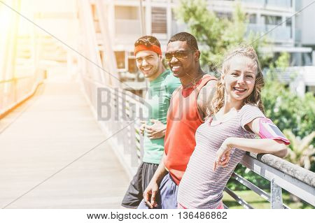 Young people runners resting after workout session on sunny day - Multi ethnic fitness friends taking break from running workout - Jogging and healthy lifestyle concept - Soft focus on girl
