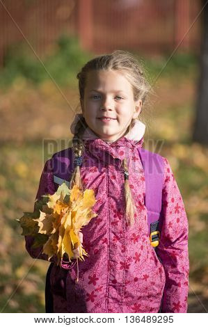 happy girl holding fallen maple leafs outdoor by autumn