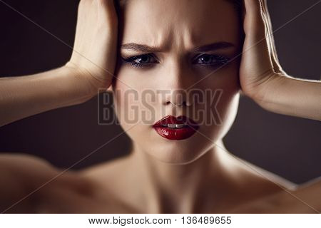 Fashion portrait of gorgeous young blond woman with red lips with worried expression on face. Shallow depth of field. Dark background