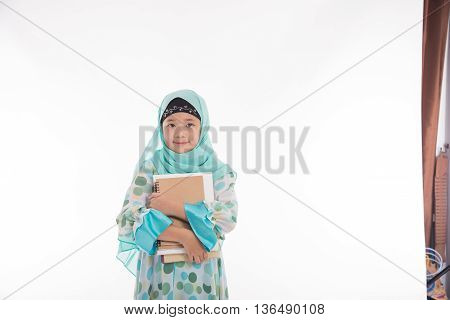 Asian muslim student holding books on white background isolated
