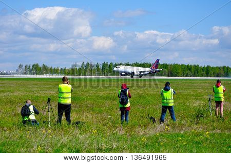 SAINT PETERSBURG RUSSIA - MAY 11 2016. Spotting fans shoot the Brussel Airlines airplane at official traditional spotting for professional and amateur aviation photographers in Pulkovo airport