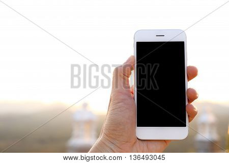Hand holding white smartphone with mountain background