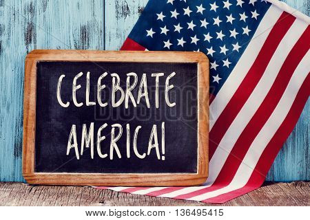 a wooden-framed chalkboard with the text celebrate America written in it and a flag of the United States, against a rustic blue wooden background