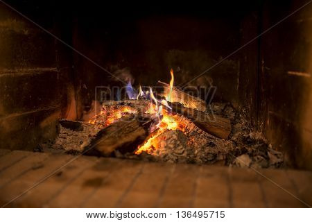 Wood fire with heaped hot ashes and flaming logs burning in a rustic open brick hearth in a low angle close up view.