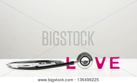 Love concept with the disc of a stethoscope forming the letter O in the word love spelled in vibrant pink letters with copy space on a light grey background.