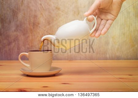 Side view of a male pouring tea