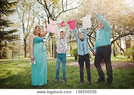 Happy Pregnant Couple With Two Sons Holding Girls' Baby Clothes On String  Background Spring Nature