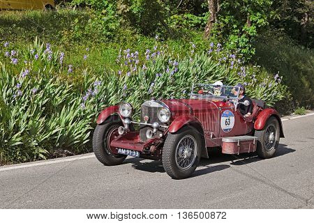 PASSO DELLA FUTA (FI) ITALY - MAY 21: driver and co-driver on a classic German car Mercedes-Benz 710 SSK (1929) travel in Tuscany during the historical race Mille Miglia on May 21 2016 in Passo della Futa (FI) Italy