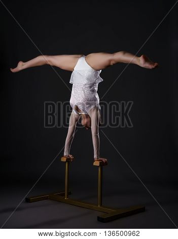 Image of charming gymnast doing handstand on circus stands