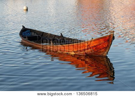 Wooden rowboat in warm evening light partly filled with water to get it waterproof