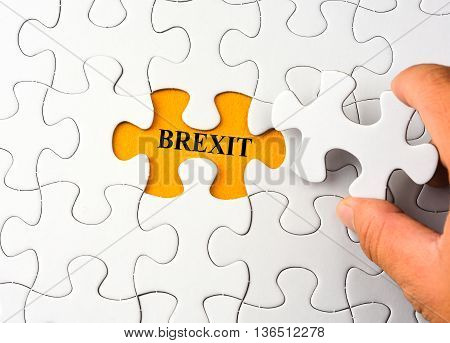 White puzzle on orange background with word brexit
