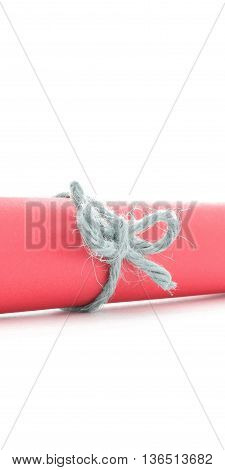 Handmade natural rope bow tied on red message roll, isolated
